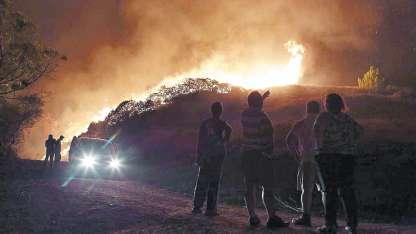Un grupo de personas observa las llamas que destruyen una casa en Obidos, Portugal.