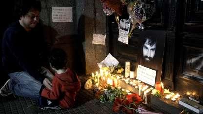 La puerta de la Morgue, cubierta de flores y velas.