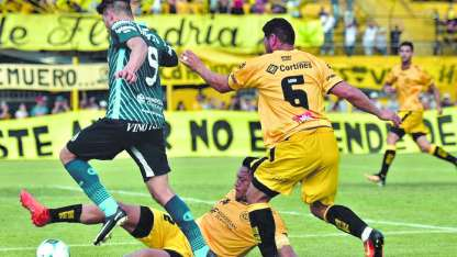Sosa, autor del segundo gol de Flandria, cierra junto a Chiqui Pérez un intento de Strhaman por el costado derecho.