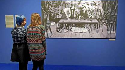 """Dos mujeres observan la foto de """"La mesa herida"""", la obra desaparecida de la mexicana."""