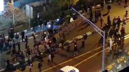 Manifestantes tiran una valla para contener el avance de la marcha en Teherán.