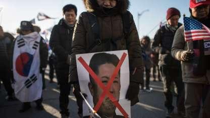 Un manifestante porta una imagen del líder norcoreano Kim Jong-Un con el rostro tachado /AFP