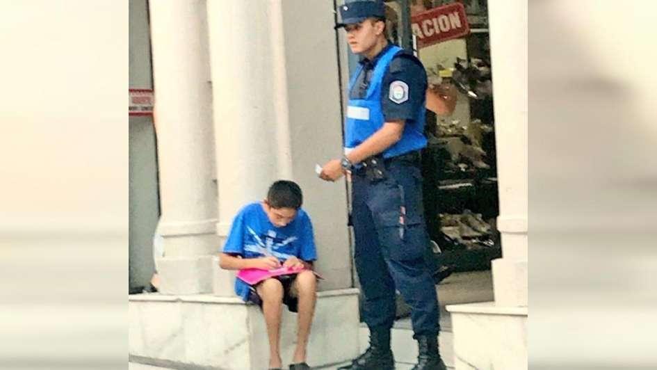 La emotiva historia de la foto de un policía que ayuda a estudiar a un nene en la calle