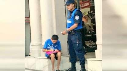 El policía Cristian Natanael Irigoitia ayuda a un nene a estudiar.