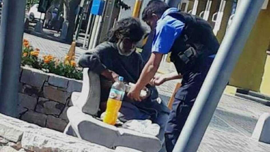 La conmovedora imagen de un policía que le brinda comida y abrigo a un indigente en Maipú