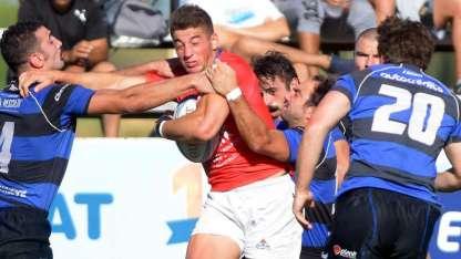 Enzo Falaschi tiene la pelota mientras dos rivales intentan arrebatársela.