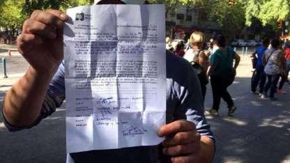 Uno de los cuidacoches muestra la multa que recibió desde la Municipalidad.
