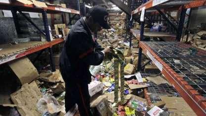 """Un guardia de seguridad observa los daños producidos tras los saqueos en un supermercado """"La Unión"""" de Managua."""
