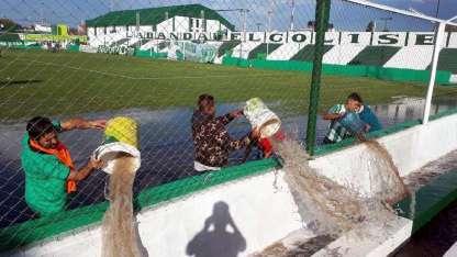 Allegados al equipo puntanto sacan el agua acumulada en la cancha, con baldes.