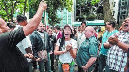 Opositores al presidente Nicolás Maduro gritan consignas contra las elecciones frente a la sede de la OEA en Caracas.