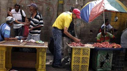 Como siempre que faltan trabajo y víveres, los vendedores ambulantes afloran, como estos que venden carne en Caracas.