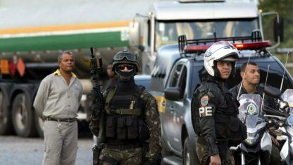 Policías y soldados se preparan para escoltar un camión de combustible que rompió la huelga, en Duque de Caixas, Río.