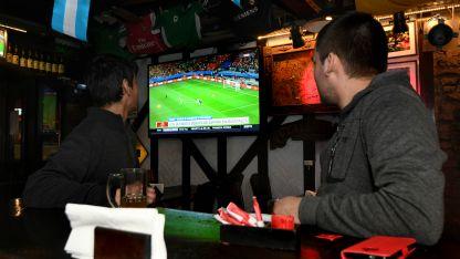 Sergio, Omar y Gonzalo ya están preparados para ver los partidos de fútbol en un bar de avenida Colón.