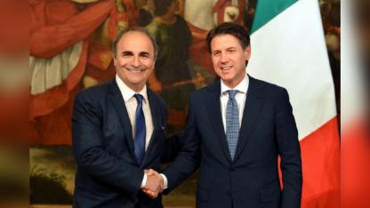 Tras asumir, Ricardo Merlo (izq.) es saludado por el premier Giuseppe Conte.