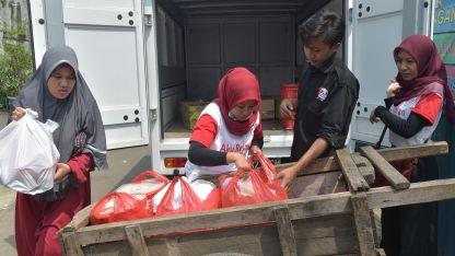 Voluntarios reparten comida entre indigentes.