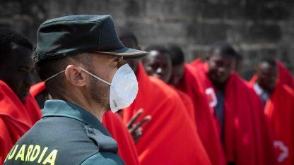 Un miembro de la Guardia Civil vigila mientras los inmigrantes llegan para ser asistidos por la Cruz Roja Española.
