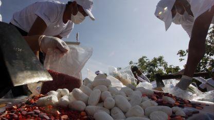 Expertos preparan pastillas de drogas para luego incinerarlas en Camboya.