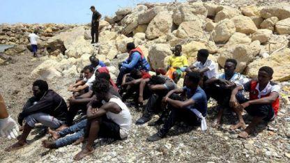 Jóvenes que llegaron a nado a la costa libia tras el naufragio de su gomón esperan la asistencia humanitaria.