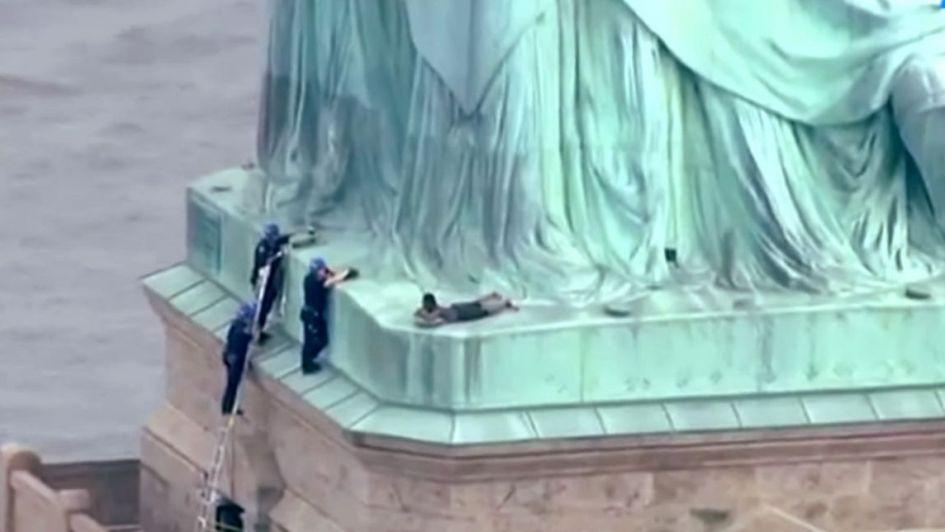 Policía escolta a persona que subió la Estatua de la Libertad
