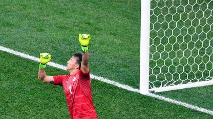 El débil remate de Griezmann resbala por los guantes y se meterá.