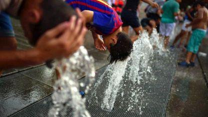 En plazas y parques de Madrid la gente se refresca con el agua de las fuentes.