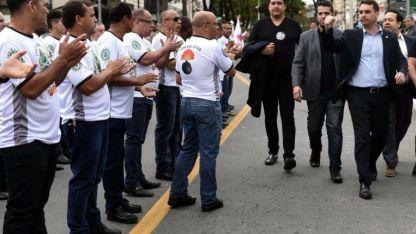 Flavio Bolsonaro (derecha) saluda a seguidores, luego de visitar a su padre en el hospital Albert Einstein de San Pablo.