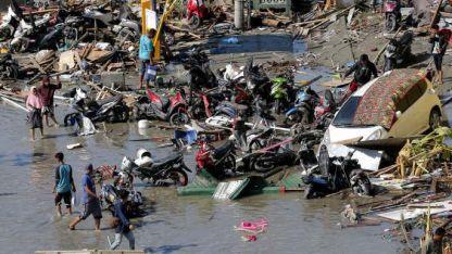 Destrucción. Las personas buscan entre los restos de Palú.