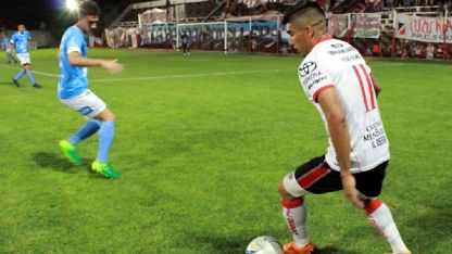 Figueredo, del Deportivo Maipú, intenta lanzar un centro ante el acecho de Suárez.
