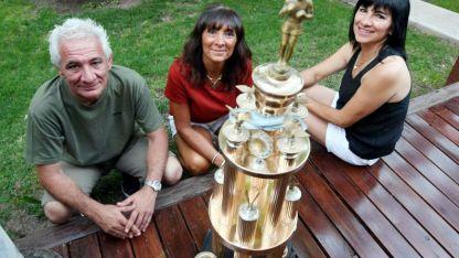 Los hijos del campeón. Lolo, Ana y Nancy junto a uno                 de los trofeos que trajo Nicolino, tras ganar el título mundial.