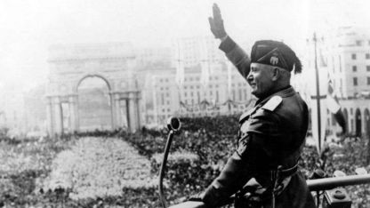 Benito Mussolini realiza su clásico saludo fascista.