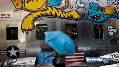 Una mujer china pasea frente a un local de ropas de una franquicia estadounidense en Beijing.