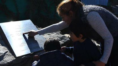 La viuda de Cussi les muestra a sus hijos la placa que lleva su nombre en Las Compuertas.