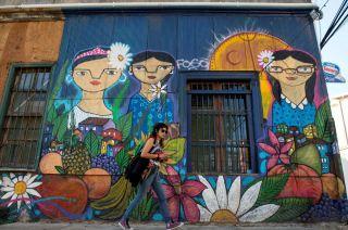 Color. Una mujer camina ante un mural en Valpo, cuyo centro histórico es Patrimonio de la Humanidad.