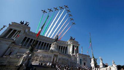 La clásica formación de aviones militares con los tres colores de la bandera italiana, sobre un edificio histórico de Roma.